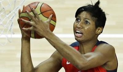 United States' Angel McCoughtry, left, sails to the basket past Australia's Belinda Snell (12) during a women's basketball semifinal game at the 2012 Summer Olympics, Thursday, Aug. 9, 2012, in London. (AP Photo/Victor R. Caivano)