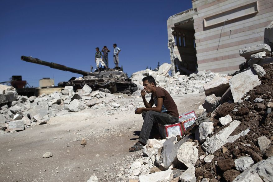 A Syrian man smokes a cigarette Aug. 22, 2012, while sitting next to the rubble of a damaged mosque in the city of Azaz, Syria, on the outskirts of Aleppo. (Associated Press)