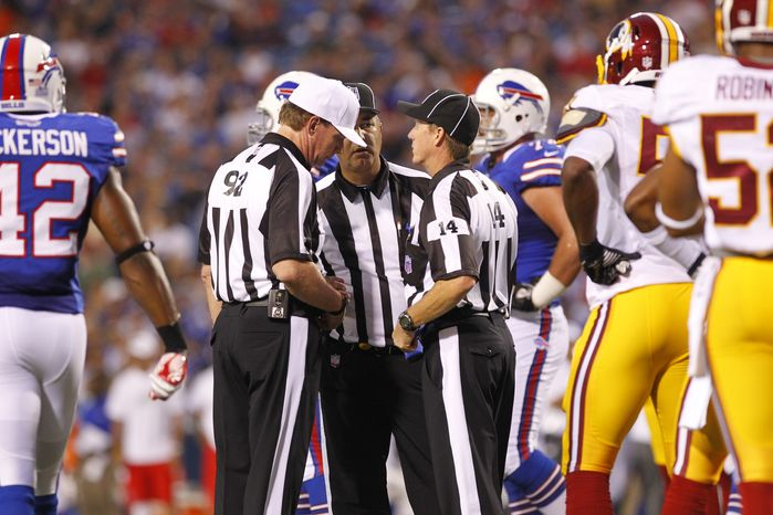 Officials confer on a ruling during an NFL football game between the Buffalo Bills and the Washington Redskins in Orchard Park, N.Y., Thursday, Aug. 9, 2012. (AP Photo/Bill Wippert)