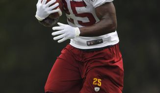 Washington Redskins running back Tim Hightower runs the ball during practice at the NFL football training camp at Redskins Park, Wednesday, Aug. 15, 2012, in Ashburn, Va. (AP Photo/Pablo Martinez Monsivais)