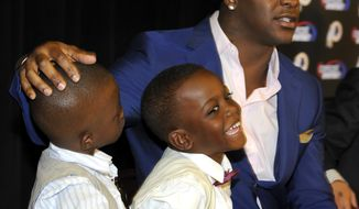 Clinton Portis reacts announces his retirement from the Washington Redskins NFL football team, with sons Camdin, left, and Chaz, both four years old, during a news conference at Redskins Park in Ashburn, Va., Thursday, Aug. 23, 2012.  . (AP Photo/Richard Lipski)