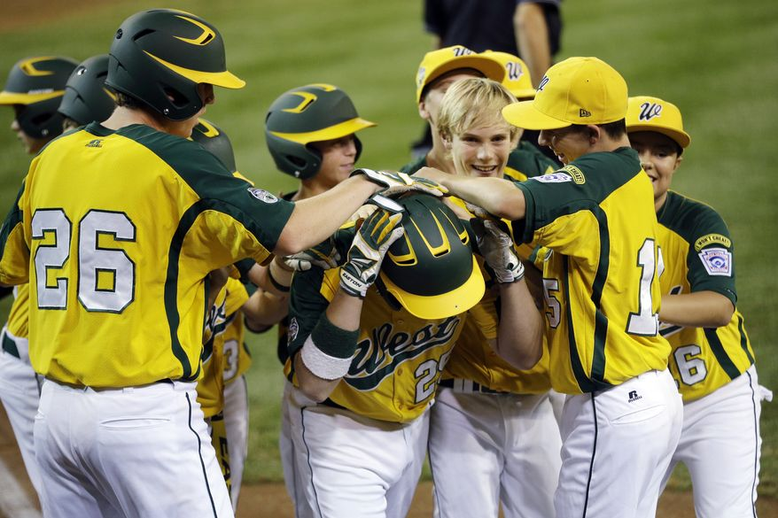 Petaluma, Calif.'s Quinton Gago, center, is mobbed by teammates after hitting a home run off San Antonio, Texas' Carter Elliott in the first inning of a baseball game at the Little League World Series, Thursday, Aug. 23, 2012, in South Williamsport, Pa. Petaluma won 11-1. (AP Photo/Matt Slocum)