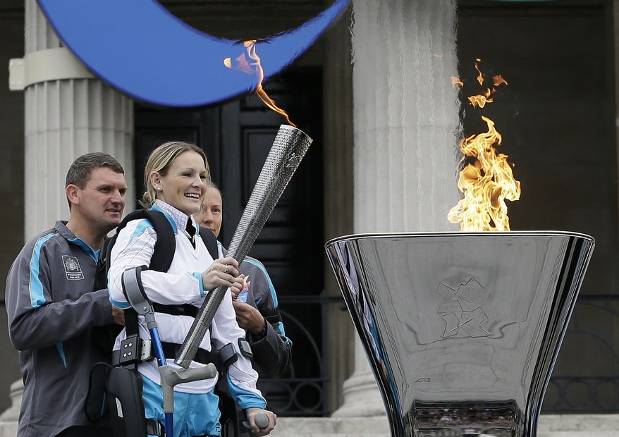 Claire Lomas lights the Paralympic flame cauldron in Trafalgar Square in London, Friday, Aug. 24, 2012. Claire had a horse riding accident in 2007 leaving her paralysed from the chest down.  The London Paralympics begin on Wednesday Aug. 29.(AP Photo/Kirsty Wigglesworth)