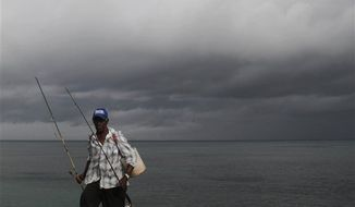 A fisherman walks home under cloudy skies along the shores of Santo Domingo, Dominican Republic, Thursday, Aug. 23, 2012. (AP Photo/Manuel Diaz)