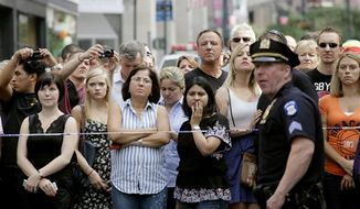 Bystanders and a police officer stand on Fifth Avenue to view the scene after a multiple shooting outside the Empire State Building, Friday, Aug. 24, 2012, in New York. Suspect Jeffrey Johnson killed a former co-worker in cold blood and then himself was shot dead by police. (AP Photo/Mark Lennihan)