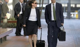 Kevin Johnson, right, and Victoria Maroulis, left, attorneys for Samsung, leave the US Courthouse and Federal building after a jury reached a decision in the Apple Samsung trial on Friday, Aug 24, 2012 in San Jose, Calif. After a year of scorched-earth litigation, a jury decided Friday that Samsung ripped off the innovative technology used by Apple to create its revolutionary iPhone and iPad. The jury ordered Samsung to pay Apple $1.05 billion. An appeal is expected. (AP Photo/Tony Avelar)