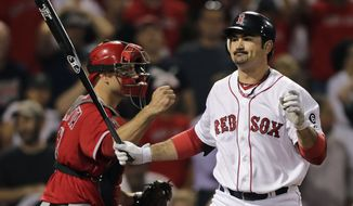 Boston Red Sox's Adrian Gonzalez, right, reacts as he strikes out swinging to end the game as Los Angeles Angels catcher Chris Iannetta pumps his fist in the bottom of the 10th inning of a baseball game at Fenway Park in Boston, Thursday, Aug. 23, 2012. The Angels defeated the Red Sox 14-13. (AP Photo/Charles Krupa)