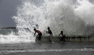 Men stand behind the seawall as waves brought by Tropical Storm Isaac splash over them in Baracoa, Cuba, Saturday, Aug. 25, 2012. Tropical Storm Isaac pushed into Cuba on Saturday after sweeping across Haiti's southern peninsula. Isaac's center made landfall just before midday near the far-eastern tip of Cuba. (AP Photo/Ramon Espinosa)