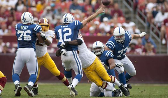 Indianapolis Colts quarterback Andrew Luck (12) is hit hard during first half action of the Indianapolis Colts at Washington Redskins preseason football game, Saturday, August 25, 2012 in Washington, DC. (Craig Bisacre/The Washington Times)