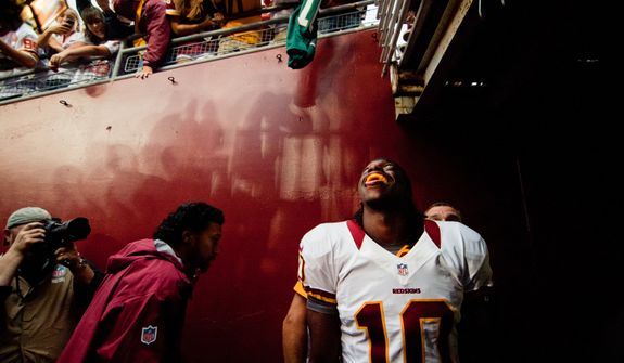 Washington Redskins quarterback Robert Griffin III (10) smiles to fans as he leaves the field of the Indianapolis Colts at Washington Redskins preseason football game, Saturday, August 25, 2012 in Washington, DC. Redskins won 30 - 17. (Craig Bisacre/The Washington Times)
