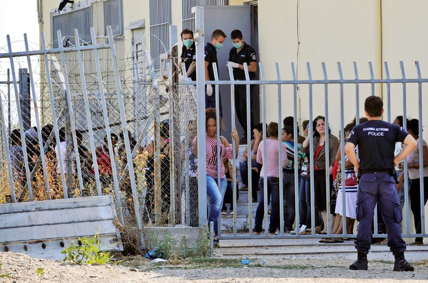 In this Thursday, Aug. 9, 2012 photo illegal immigrants are seen at detention center in Filakio village, northern Greece, near the borders with Turkey. Greece launched an aggressive campaign this month to try to seal its 200-kilometer (130-mile) northeastern border, as it faces a debilitating financial crisis that has caused a swell in joblessness and a surge in racist attacks against immigrants with dark skin. (AP Photo/Nikolas Giakoumidis)