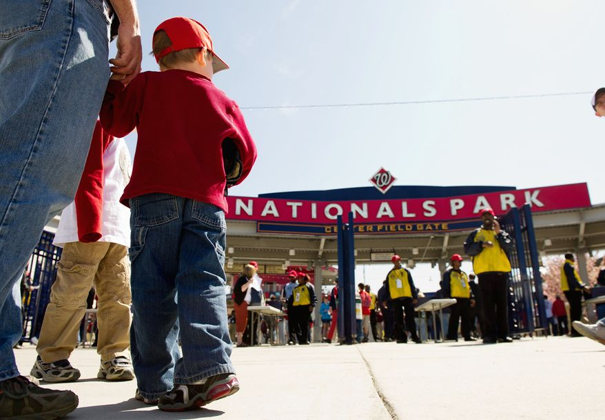 Fans have been flocking to Nationals Park this season, starting with Gavin Kearney, 4, holding the hand of his father, Gus, at the April 3 exhibition game against Boston. (Andrew Harnik/The Washington Times)