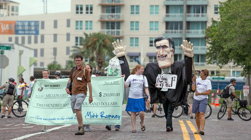 Members of a Florida consumer activism group Sunday march down the streets of Tampa, Fla., with a giant Mitt Romney puppet. Republican National Convention protesters, many of whom have camped outdoors, said the wind and rain expected Monday from Tropical Storm Isaac would not deter their plans for the week. Tampa officials warned that if safety becomes a concern, people will be ordered off the streets. (Andrew S. Geraci/The Washington Times)