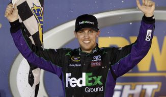 Denny Hamlin smiles in victory lane after winning the NASCAR Sprint Cup Series auto race Saturday, Aug. 25, 2012, in Bristol, Tenn. (AP Photo/Mark Humphrey)