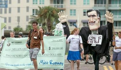 Members of the Florida Consumer Action Group march down the streets of Tampa with a giant Mitt Romney foam character protesting the '1%', in Tampa, Fla., Sunday, August 26, 2012.  (Andrew S. Geraci/The Washington Times)