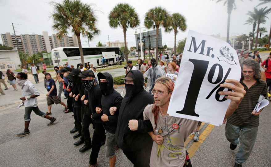 Demonstrators march in downtown St. Petersburg, Fla. The protestors were demonstrating outside Tropicana Field where a welcoming event is taking place for the delegates of the Republican National Convention  (AP Photo/Dave Martin)