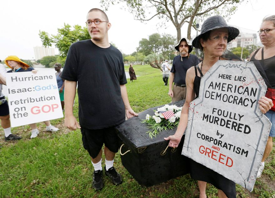 Morgan Wright, of St. Petersburg, Fla., second from right, walks with a mock coffin with friends during a protest march,  Sunday, Aug. 26, 2012, in St Petersburg, Fla. Hundreds of protestors gathered a park in downtown St. Petersburg  to march in demonstration against the Republican National Convention. (AP Photo/Patrick Semansky)