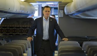 Republican presidential candidate Mitt Romney answers a question after landing in Portsmouth, N.H., on Saturday, Aug. 25, 2012. (AP Photo/Evan Vucci)