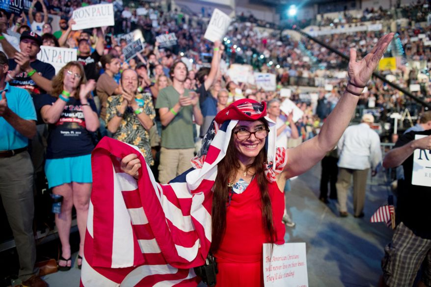 Melina Brajovic, covered in an American flag, and other supporters, listen to Ron Paul speak.   (Andrew Harnik/The Washington Times)