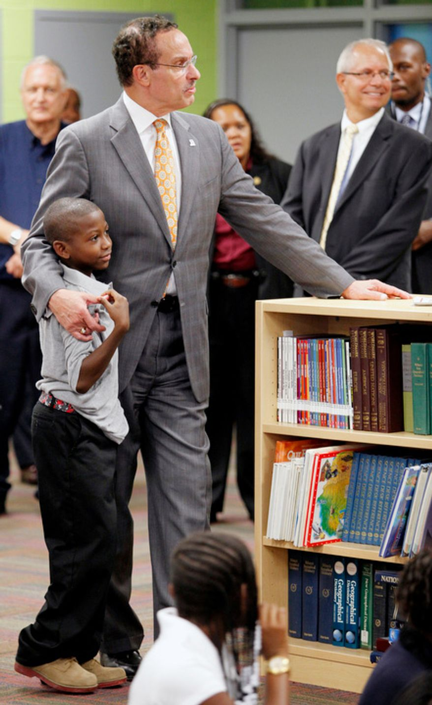 Mayor Vincent C. Gray gets a hug from Phillip Thomas, 9, to kick off his visit to Amidon-Bowen Elementary School in the District.