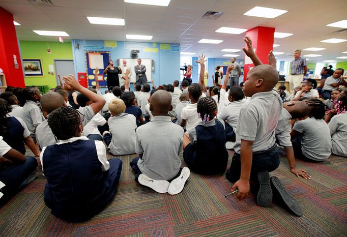 Fifth-grader Tywon Malcom (right) waits for his turn to ask a question during D.C. Mayor Vincent C. Gray's visit to Amidon-Bowen Elementary School in the District on the first day of class on Aug. 27, 2012. The mayor, D.C. Schools Chancellor Kaya Henderson, and Department of General Services Director Brian Hanlon visited the school.