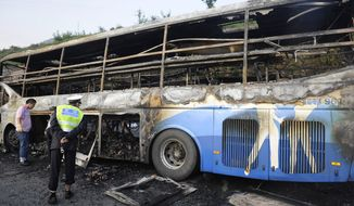 A policeman looks at a burned double-decker sleeper bus on Aug. 26, 2012, after it collided with a tanker loaded with highly-flammable methanol on an expressway in Yan'an in northwest China's Shaanxi province, causing both vehicles to burst into flames and killing 36 people, state media said. (Associated Press)
