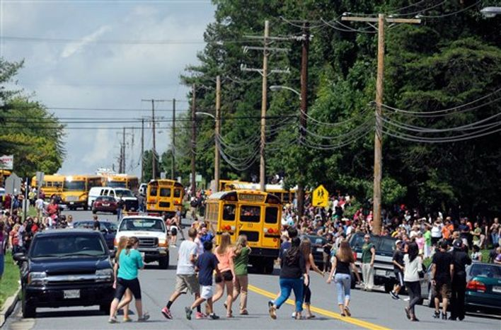 Parents and students try to reunite after a student was shot and critically wounded on the first day of classes at Perry Hall High School, Monday, Aug. 27, 2012, in Perry Hall, Md. A suspect was taken into custody shortly after the shooting, according to police. No one else was reported injured. (AP Photo/Steve Ruark)