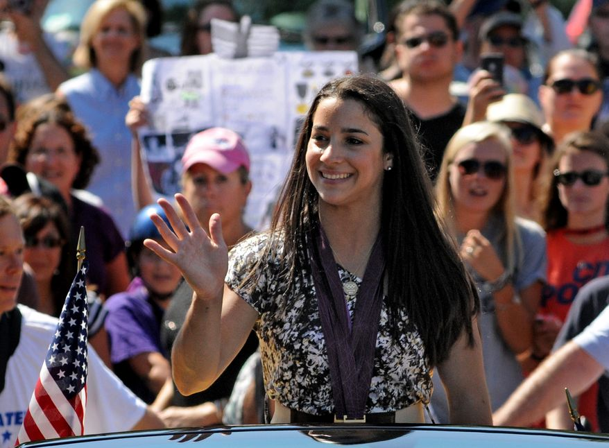 Olympic gold-medal gymnast Aly Raisman waves to the crowd during a parade in her honor in Needham, Mass., on Sunday, Aug. 26, 2012. Raisman, 18, won two gold medals and a bronze at the London Summer Olympics. (AP Photo/The Boston Herald, Faith Ninivaggi)  BOSTON GLOBE OUT; METRO BOSTON OUT; MAGS OUT; ONLINE OUT