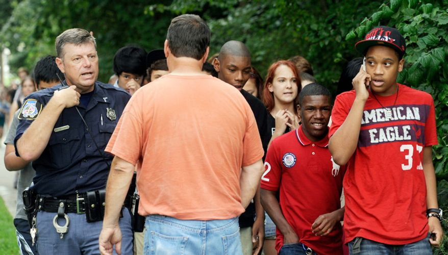A Baltimore County police officer speaks to a parent as students are evacuated from Perry Hall High School after a student was shot and critically wounded on the first day of classes Monday, Aug. 27, 2012, in Perry Hall, Md.  (AP Photo/Steve Ruark)