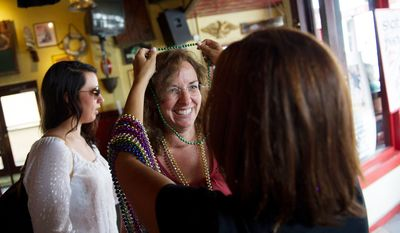 Ann Miller (left) an alternate delegate from Baltimore County Maryland receives Mardi Gras style beads from fellow alternate delegate from Baltimore County, Maryland Gloria Murphy, as they and other delegates from Maryland take shelter from the spotty rain at Gaspar's Grotto as tropical storm Isaac delays the kickoff of Republican National Convention in Ybor City, Fla.  (Rod Lamkey Jr./The Washington Times)