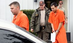 **FILE** U.S. Army Sgt. Anthony Peden (left), 25, and Pvt. Isaac Aguigui, 19, are led away in handcuffs Dec. 12, 2011, after appearing before a magistrate judge at the Long County Sheriff's Office in Ludowici, Ga. Peden and Aguigui are two of four soldiers in Georgia charged with killing a former comrade and his girlfriend to protect an anarchist militia group they formed that stockpiled assault weapons and plotted a range of anti-government attacks. (Associated Press)