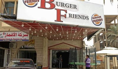 A customer stands outside Burger Friends restaurant. An Iraqi doctor said he fears the popularity of American-style food will make children fatter. Iraqi entrepreneurs and foreign investors are driving the food craze.