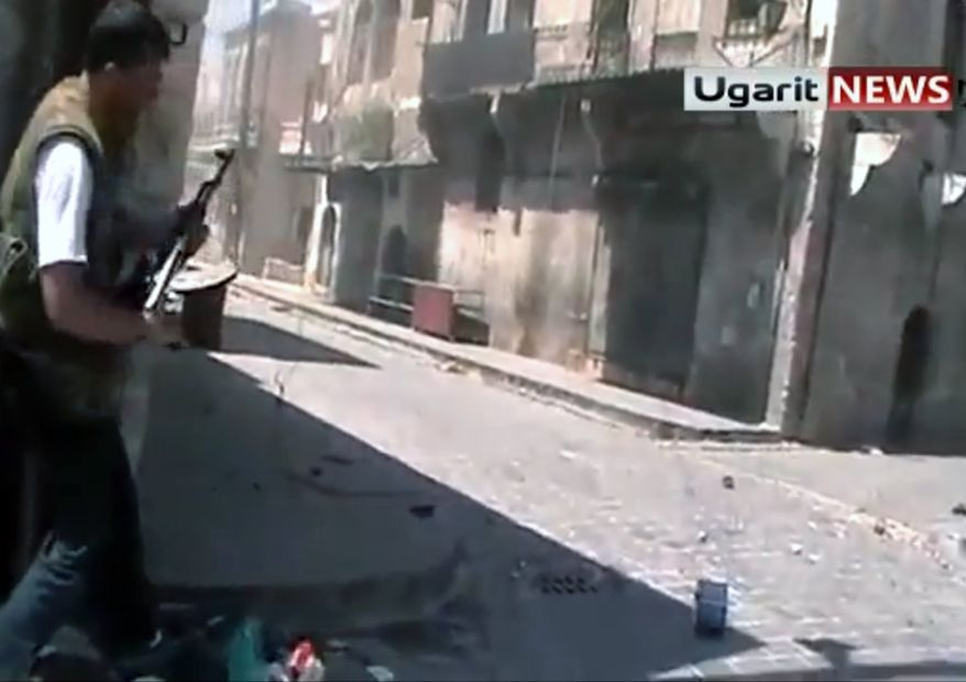 ** FILE ** In this frame grab made from amateur video provided by Ugarit News, taken on Sunday, Aug. 26, 2012, purports to show a member of the rebel group, the Unification Brigade, as he prepares to fire his weapon at a group of Assad soldiers in street fighting in Aleppo, Syria. The Associated Press is unable to independently verify the authenticity, content, location or date of this citizen journalist image. (AP Photo/Ugarit News via AP video)