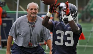 Virginia defensive coordinator, Jim Reid, left, plays defender as tailback, Perry Jones (33) hauls in a pass during practice in Charlottesville, Va., Monday, Aug. 6, 2012.  ( AP Photo/Steve Helber)