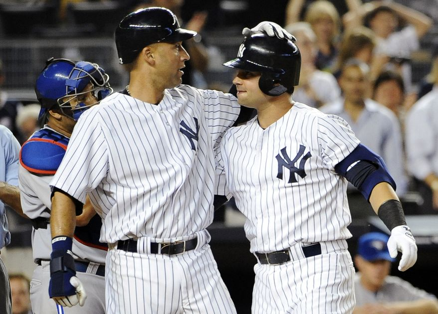 New York Yankees' Derek Jeter, left, greets Nick Swisher at home plate after Swisher hit a two-run home run off of Toronto Blue Jays' Aaron Laffey that scored Jeter in the fifth inning of a baseball game, Monday, Aug. 27, 2012, at Yankee Stadium in New York. (AP Photo/Kathy Kmonicek)