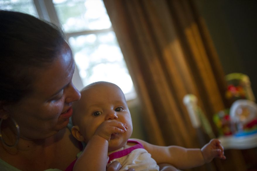 Sofia Carr are plays with her youngest daughter Olivia, 8 months after dinner at their home in Downingtown, Pa.  (Rod Lamkey Jr./The Washington Times)