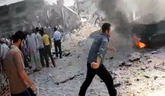 In this image made from amateur video released by the Shaam News Network and accessed Aug. 28, 2012, Syrian men stand near a burning car due to shelling in Kfarnebel, Idlib province, northern Syria. (Associated Press/Shaam News Network via AP video)
