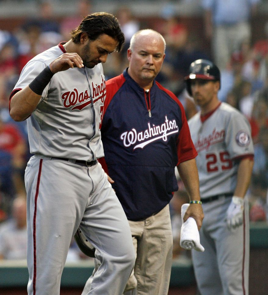 Washington Nationals' Michael Morse, left walks off the field after being hit by a pitch while playing against the Philadelphia Phillies in the first inning of a baseball game on Friday, Aug. 24, 2012, in Philadelphia.  (AP Photo/H. Rumph Jr)