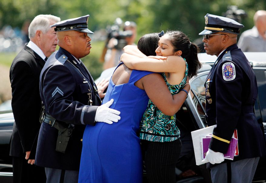 Zarina Meer (right) hugs a woman she identified as the mother of Prince George's County police officer Adrian Morris, after Morris' funeral service at Woodstream Church in Mitchellville, MD, on August 28, 2012. Morris died in the line of duty on August 20, 2012. (Eva Russo/Special to The Washington Times)