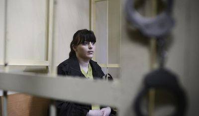 Russian opposition activist Taisiya Osipova sits in the defendant's cage in a courtroom in the western Russian city of Smolensk on Tuesday, Aug. 28, 2012. She was sentenced to eight years in prison on drug charges, her husband said, in a ruling that drew immediate opposition outrage. (AP Photo/Mitya Aleshkovskiy)