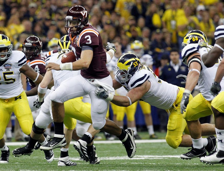 Virginia Tech quarterback Logan Thomas (3) carries as Michigan defensive end Ryan Van Bergen (53) tries to tackle during the second quarter of the Sugar Bowl NCAA college football game in New Orleans, Tuesday, Jan. 3, 2012. (AP Photo/Bill Haber)