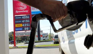 ** FILE ** In this August 2012 file photo, a driver in Kalamazoo, Mich., pumps gas near a sign showing a gallon of regular costing $4.09. (Associated Press)