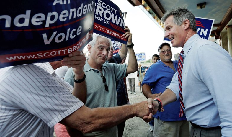 Sen. Scott P. Brown, Massachusetts Republican, greets voters in Dedham, Mass.. He is seeking re-election as more of a centrist than a tea party favorite, a status that aided his candidacy last time. (Associated Press)