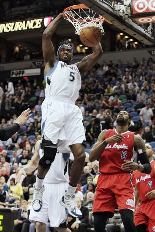Minnesota Timberwolves small forward Martell Webster (5) dunks the ball while Los Angeles Clippers center DeAndre Jordan (6) watches during the first quarter of an NBA basketball game, Thursday, April 12, 2012, in Minneapolis. (AP Photo/Genevieve Ross)