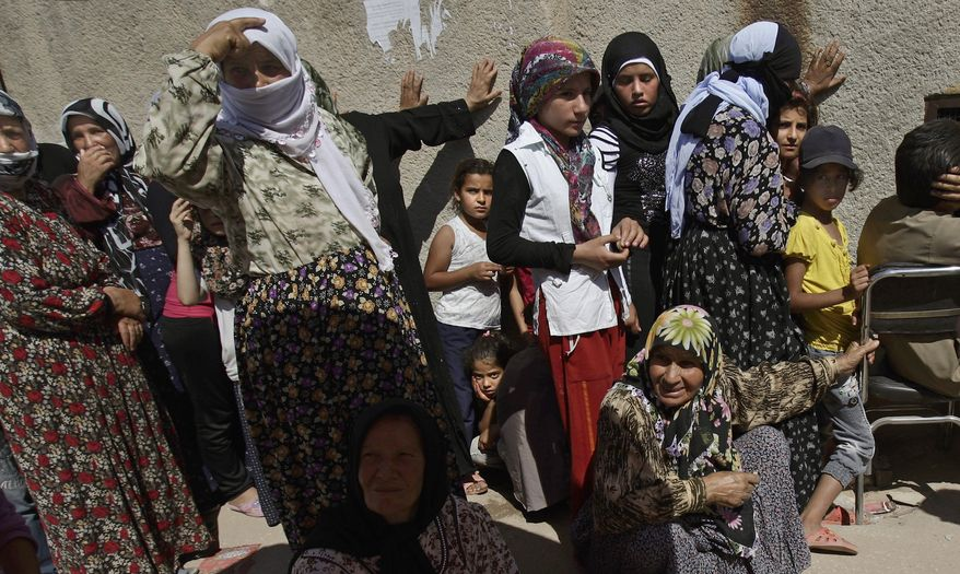 Syrian women and children wait Aug. 28, 2012, outside a bakery shop to buy bread in Azaz, Syria. (Associated Press)