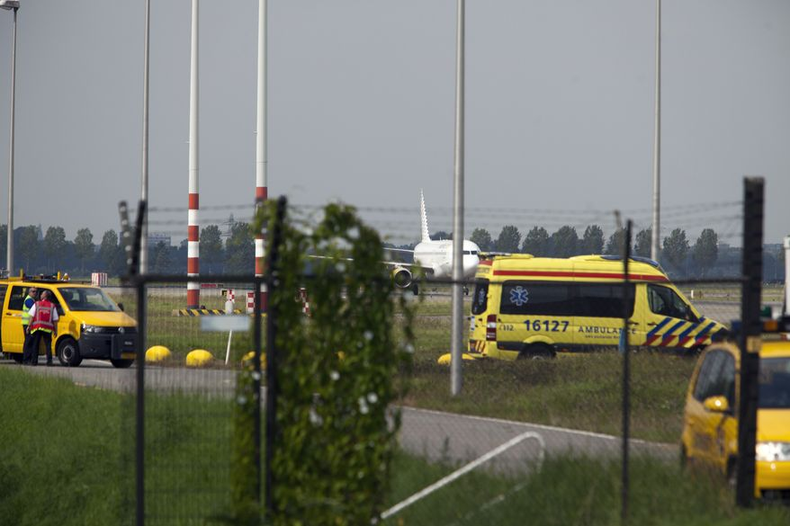 An ambulance sits in front of a Vueling jetliner that arrived from Malaga, Spain, at Amsterdam's Schiphol Airport on Wednesday, Aug. 29, 2012. (AP Photo/Cris Toala Olivares)