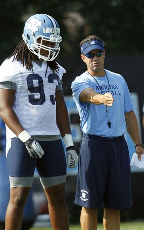 In this photo taken Friday, Aug. 3, 2012, North Carolina coach Larry Fedora, right, speaks with Tim Jackson  during an NCAA college football practice in Chapel Hill, N.C. North Carolina finally has some certainty as it opens the season under new coach Larry Fedora _ including the knowledge that the Tar Heels won't play in a bowl game no matter how many games they win.  (AP Photo/Gerry Broome)