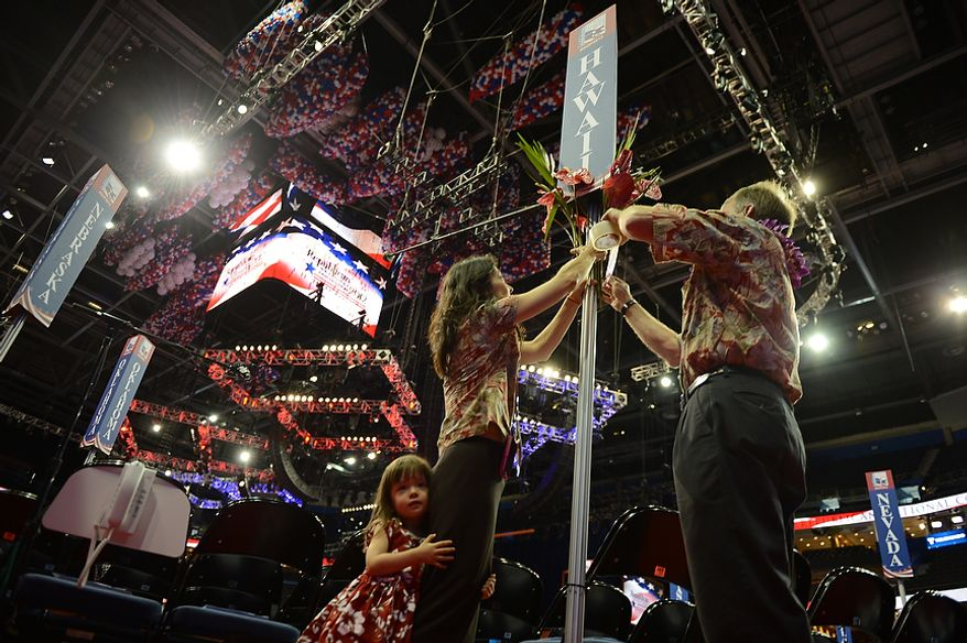 Alternate Delegate Sharin Burton, left, her husband Brad Burton, alternate Delegate, and their daughter Ellie Burton, 2, of Honolulu decorate the state placard marking their seats which, along with most Blue States, are among the furthest from the stage at the Republican National Convention at the Tampa Bay Times Forum in Tampa, Fla. on Wednesday, August 29, 2012. (Andrew Harnik/ The Washington Times)