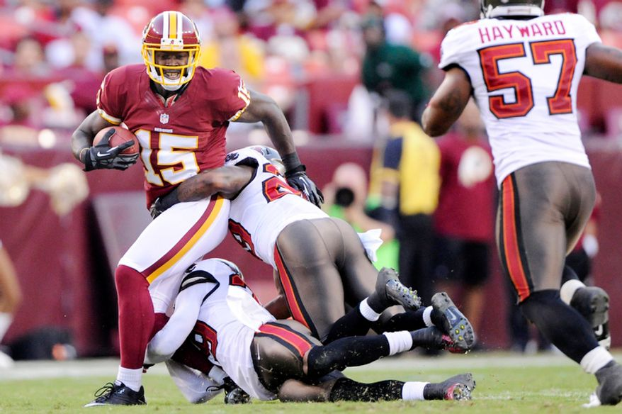 Washington Redskins wide receiver Josh Morgan (15) turns upfield against Tampa Bay Buccaneers cornerback Leonard Johnson (29) and Tampa Bay Buccaneers defensive back Brandon McDonald (39) for a first down reception during second quarter action. (Preston Keres/Special to The Washington Times)