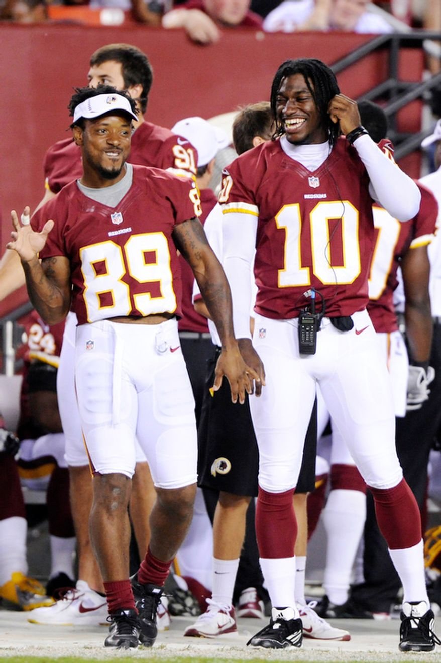 Washington Redskins wide receiver Santana Moss (89) and quarterback Robert Griffin III (10) joke on the sideline during the first half. (Preston Keres/Special to The Washington Times)